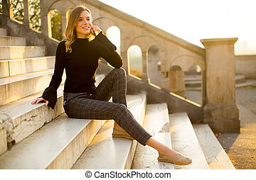 Young woman holding mobile phone while sitting on the stairs outdoor
