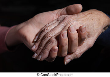 Young Woman Holding Older Woman's Hand