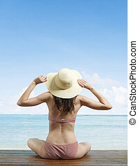 Young Woman Holding onto Sunhat on Beach