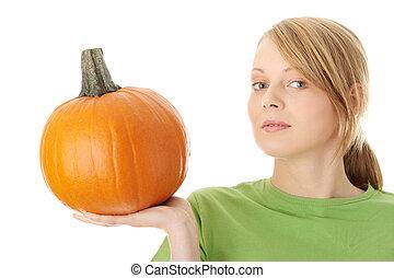 Young woman holding orange pumpkin
