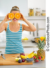 Young woman holding orange slices in front of eyes