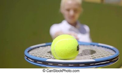 Young woman holding out a tennis ball