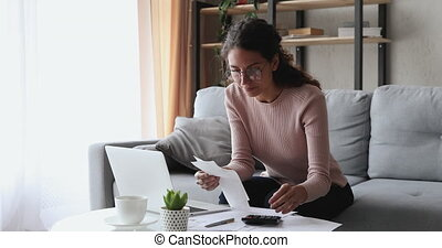 Young woman holding paper bills or paychecks calculating money expenses, tax refund, planning budget at home. Female housewife using laptop and calculator for financial accounting internet payments.