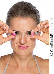 Young woman holding pills in front of eyes
