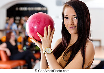 Young Woman Holding Pink Ball in Bowling Club