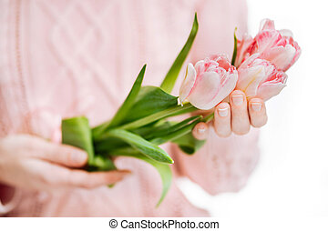 Young woman holding pink tulips on a white background.