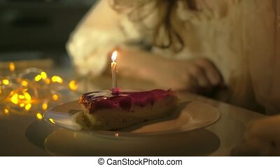 Young woman holding plate with tasty birthday cake against...