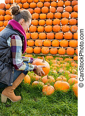 Young woman holding pumpkin. rear view