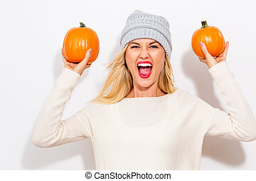 Young woman holding pumpkins