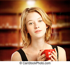 Young woman holding red coffee mug