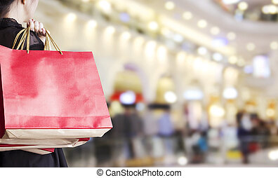 Young woman holding red shopping bag at department store