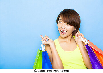 young  woman holding shopping bags and looking side