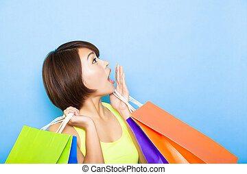 young  woman holding shopping bags and looking up