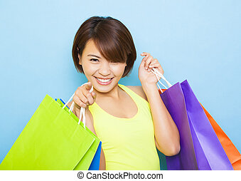 young  woman holding shopping bags before blue background