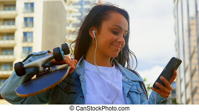 Young woman holding skateboard while using mobile phone in the city 4k