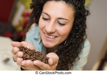 young woman holding some coffee beans in her hand