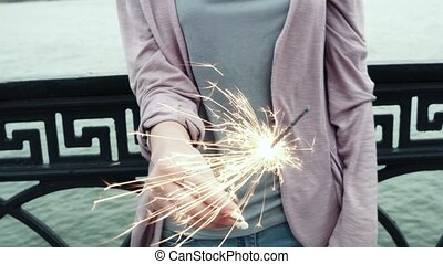 Young woman holding sparkler in city celebrating holiday,...