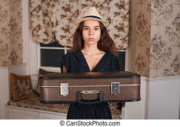 Young woman holding suitcase in her hands.