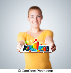 Young woman holding tablet with colorful graphs and diagrams...
