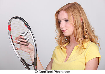 Young woman holding tennis racquet