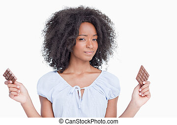 Young woman holding two pieces of chocolate
