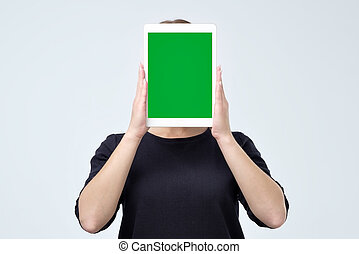 Young woman holding up a blank tablet in front of her face with the screen with copy space