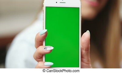 Young woman holding up her phone.