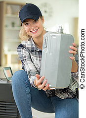 young woman holding water container of the humidifier