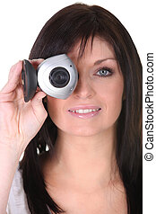 Young woman holding webcam on white background