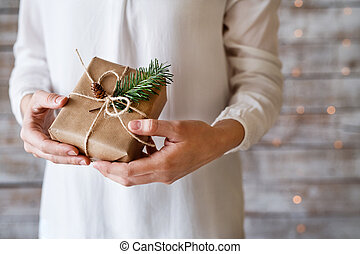Young woman holding wrapped Christmas present.