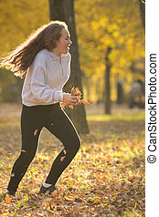 Young woman holding yellow leaves and running in the autumn park