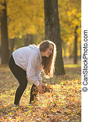 Young woman holding yellow leaves in the autumn park