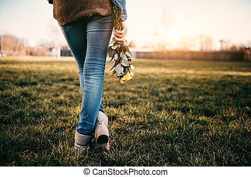Young woman holding yellow rose