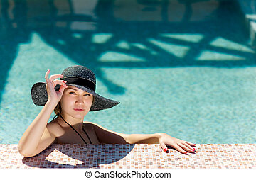 young woman holds a dark hat with large brim and peeps out of the pool