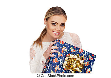 woman holds a gift wrapped in christmas paper