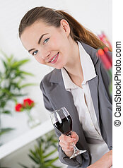 young woman holds a glass of red wine