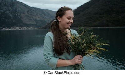 Young woman holds bouquet of mimosa, inhales fragrance near...