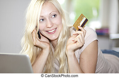 young woman holds credit card