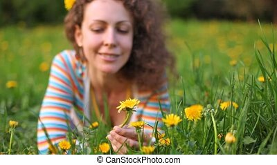 Young woman holds dandelion which water from plastic bottle