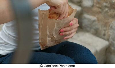 Young woman holds fresh bun in hands sitting on bench outside.