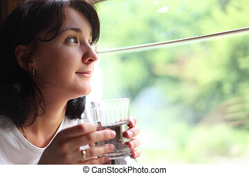 young woman holds glass andlooks in train`s window