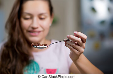 Young woman holds in the air a spoon with chocolate flakes and milk, about to eat them.