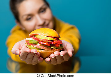 young woman holds out a veggie burger