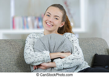 young woman hugging a pillow