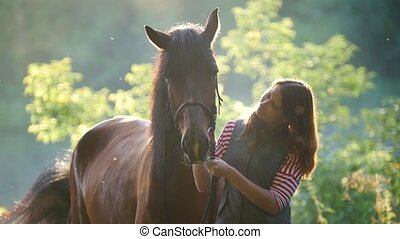 Young woman hugging and stroking a horse in the forest at...
