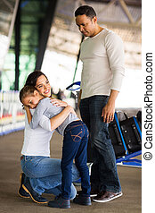 young woman hugging her daughter at airport - adult woman...