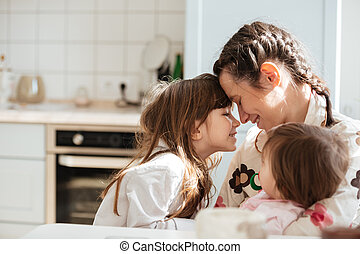 Young woman hugging her daughters while they sitting in...