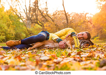 Young woman hugging her Dog in the Park