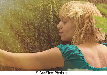 Young woman hugging the tree in forest.