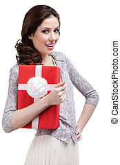 Young woman hugs a gift wrapped in red paper, isolated on white